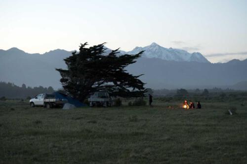 Neuseeland-Berge-Strand-Blaue-Stunde-Feuer-Menschen-Autos