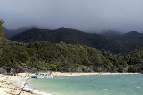 Neuseeland-Strand-Berge-Regen-Boot